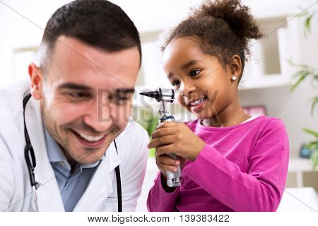 Little African Girl Holding Otoscope And Playing With Pediatrician