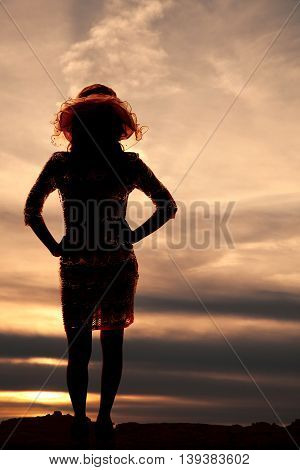 A silhouette of a woman standing in the night with her hands on her hips with a hat on .