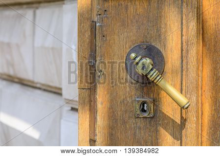Horizontal View With Old Doors Closeup. Old Doorknob At Wood Front Door And Gray Wall..