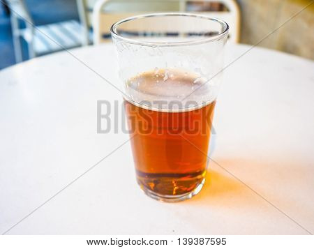 High dynamic range (HDR) Pint of British ale on a pub table - selective focus on beer over blurred background poster