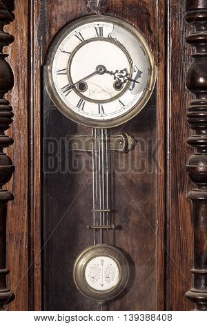 Old broken vintage grandfather clock behind a glass cover