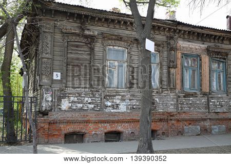 Old wooden abandoned building with carving in Samara at spring day, Russia