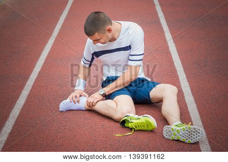 Jogger hands on foot. He is feeling pain as his ankle or foot is broken or twisted. Accident on running track during the morning exercise. Sport accident and foot sprain concepts. poster