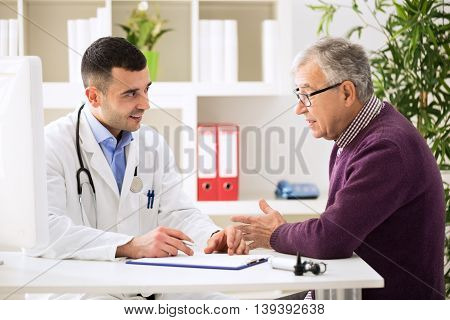 Doctor Listening To Patient Explaining His Painful