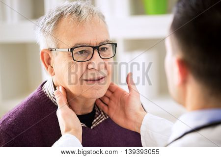 Doctor Examining Old Patient Lymph Glands