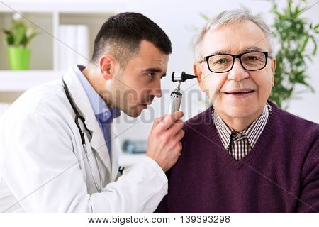 Doctor Holding Otoscope And Examining Patient Ear