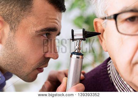 Otologist Looking Through Otoscope