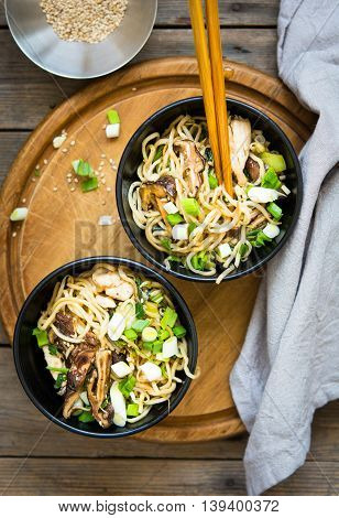 Two bowls of chicken chow mein with shiitake