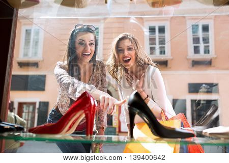 Two surpriced girl showing on elegant shoes shopping time
