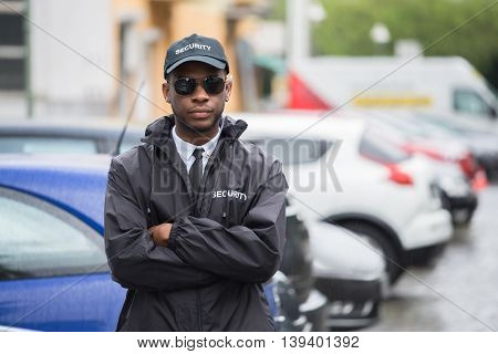 Portrait Of Young African Male Security Guard In Uniform Standing Arms Crossed On Street