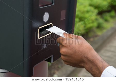 Close-up Of Person's Hand Inserting Ticket Into Parking Meter To Pay For Parking