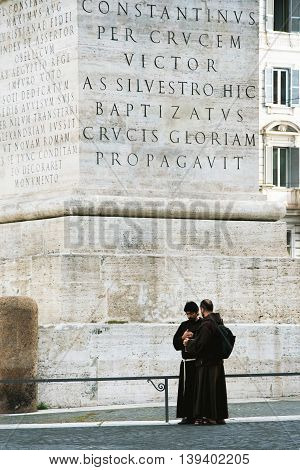 ROME, ITALY, MAY 09, 2012:  Two monks under Constantine obelisk - the largest monolith in the world