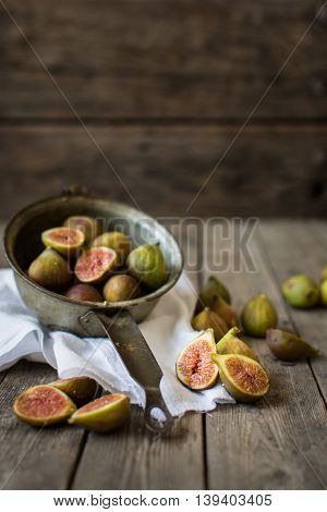 A vintage strainer filled with fresh figs