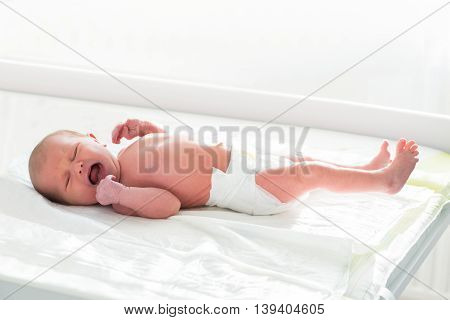 Cute Newborn Baby Crying On The Bed