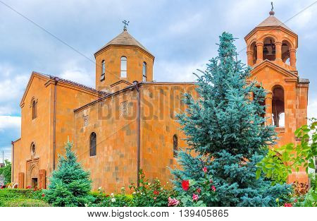 The Church of St John the Baptist built of red tuff and surrounded by the beautiful garden with the rosebushes Yerevan Armenia.