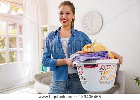 Smiling housewife posing with iron and basket with clean laundry