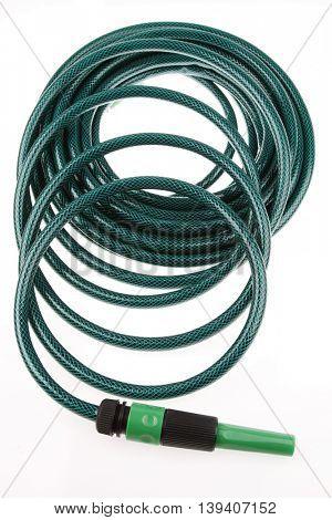 Garden hose coiled on plain background
