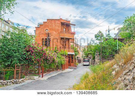 The red tuff cottage surrounded by the scenic garden with wild rose bushes in blossom Yerevan Armenia.