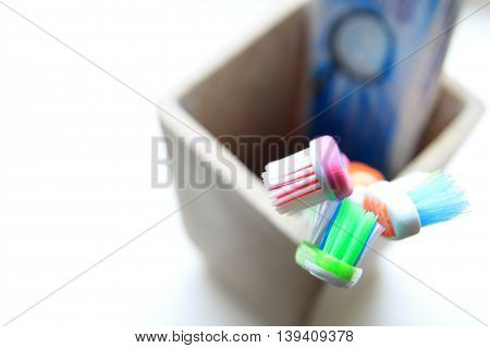 Shallow DOF shot of three toothbrushes and toothpaste in a clay tumbler in the morning light poster