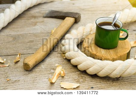 metall cup of tea with axe on wooden background