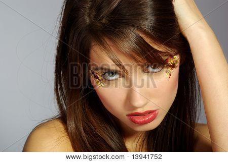 portrait of a beautiful brunette woman wearing black shirt over grey background, fashion shot. beautiful make-up