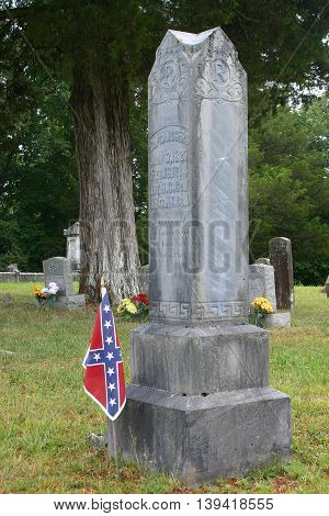 a small Confederate flag planted in front of a gravestone