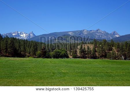 The Bitterroot mountains provide a beautiful background for forest and ranches in the valley with the same name as the mountains.