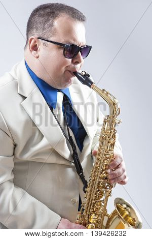 Male Saxo Player in Sunglasses Performing Expressively in Studio. Vertical Image Orientation
