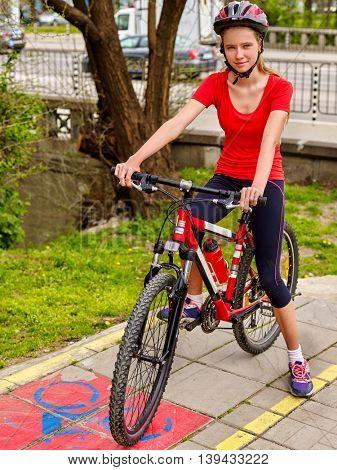 Bike bicyclist girl. Girls wearing bicycle helmet rides bicycle. Girl on bicycle rides on yellow bike lane. Bike share program save money and time.