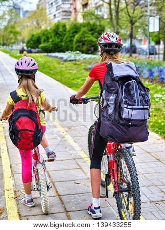 Bikes bicyclist girl. Girls wearing bicycle helmet and rucksack ciclyng bicycle. Girls children cycling on yellow bike lane. Bike share program save money and time at city street. Back view.