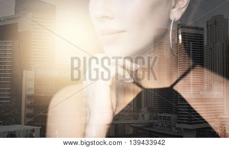 people, luxury, jewelry and fashion concept - beautiful woman in black wearing diamond earring and ring over dubai city background with double exposure and highlight