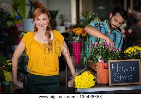 Female florist standing while male florist arranging flower bouquet in the flower shop