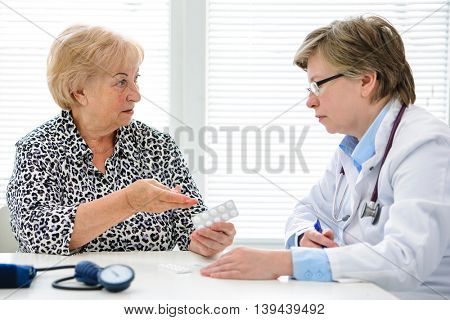 Mature woman complaining to doctor about prescribed drugs