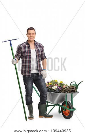 Full length portrait of a young gardener posing by a wheelbarrow with gardening equipment isolated on white background