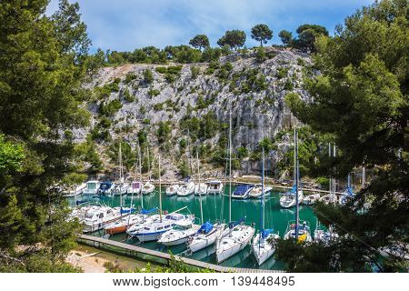 Calanque  - small fjords between Marseille and Cassis. Good weather in May. White sailboats moored in rows near woody shore