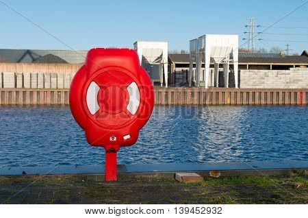 Safety life buoy in red case in a harbor