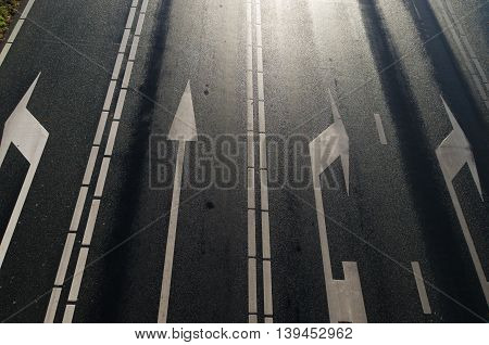 high point of view on a multi lane asphalt road with white arrows