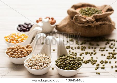 collection set of beans, legumes, peas, lentils on ceramic spoons on  wooden background