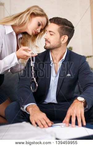 Young sensual secretary holding handcuffs for boss in office
