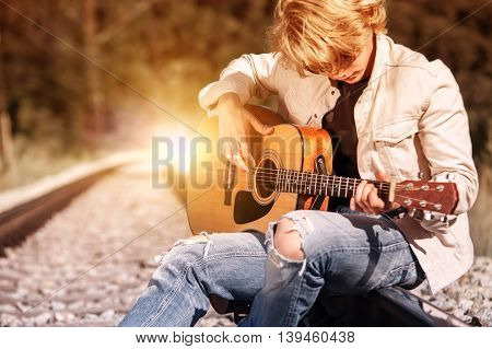 Railway blues. Young man plaing on guitar on the railway