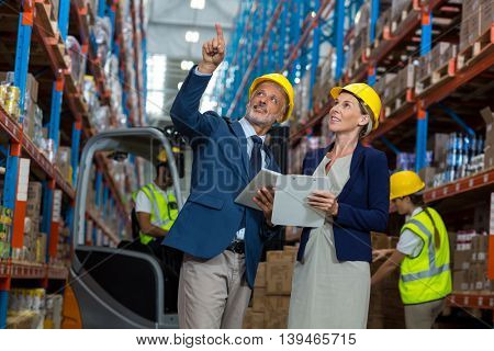 Portrait of managers are pointing and looking shelves in a warehouse