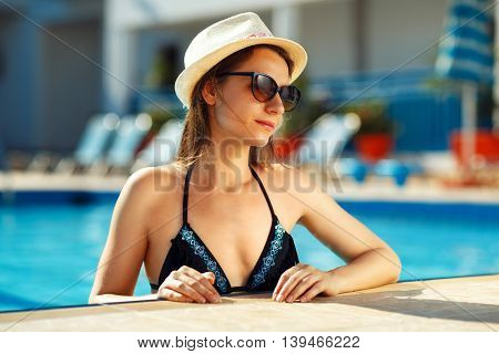 Beautiful sexy girl with healthy skin in bikini sunglasses and hat relaxing in swimming pool water in resort spa hotel on travel holidays vacation