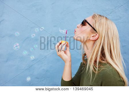 Side view shot of attractive female model blowing soap bubbles. Young woman having fun against blue background.