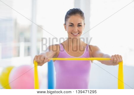 Portrait of happy woman exercising with resistance band at fitness studio