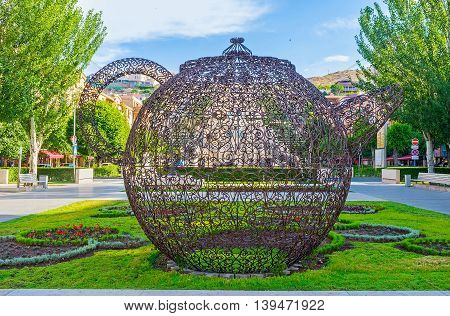 YEREVAN ARMENIA - MAY 29 2016: The giant teapot made of the metal lace located in the flower bed in the sculpture garden in Tamanyan street on May 29 in Yerevan.