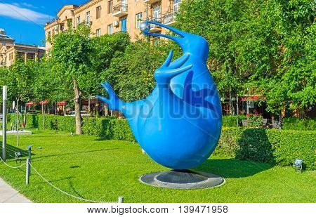 YEREVAN ARMENIA - MAY 29 2016: The blue kiwi holding the metal ball in beak in Cafesjian sculpture garden on May 29 in Yerevan.