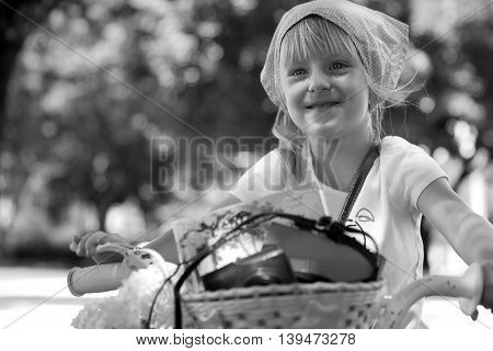 Nice little girl riding her bike on a road