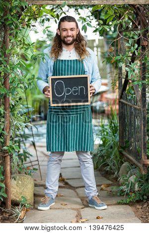 Portrait of happy young gardener holding open text chalkboard at community garden