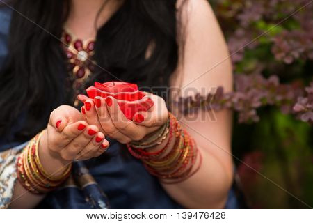 Female hands with unlit candles in form of roses in garden, close up