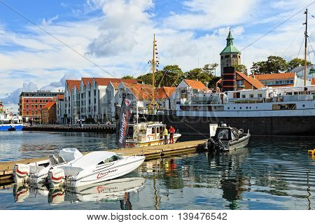 STAVANGER, NORWAY - JULY 15, 2015: View of the famous wharf and harbor front with people and a cruise ship in Stavanger, Norway. Stavanger is one of most famous cruise travel destinations in Europe.